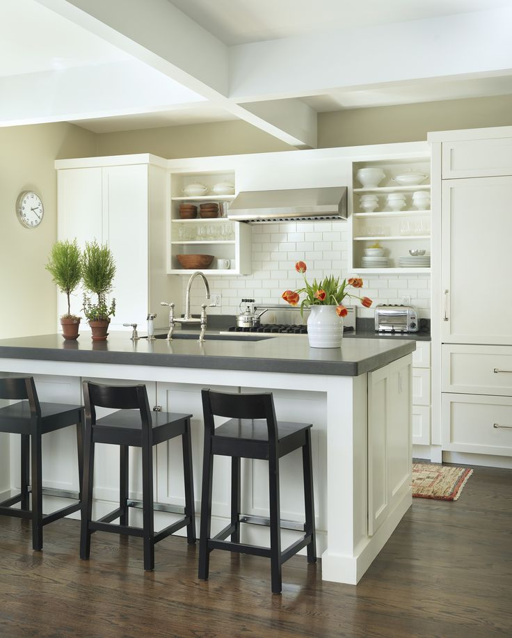 inspired by The Barefoot Contessa's kitchen (but on a much smaller scale!)...Open kitchen concept to dining and living room includes: support beams, Caesarstone, creamy white cabinetry, dark wood flooring, hidden fridge, open shelving.
