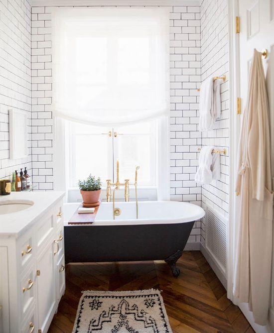 white brick wall, freestanding bathtub, wood floor, sink vanity