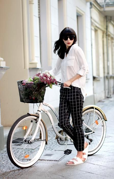 Patterned Pants: 20 Outfit Inspiration Photos - cool minimalist outfit with an oversized white blouse, checkered black and white pants, + white Birkenstock sandals—not to mentioned the chic white bike and basket full of flowers!