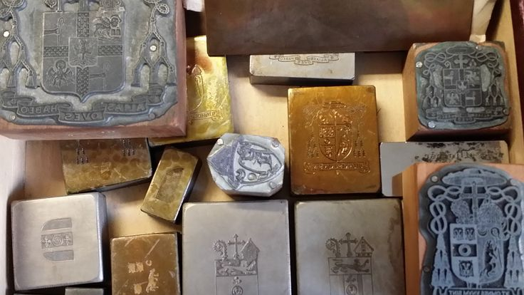 "An assortment of printing plates, stored in the Diocesan Archives, includes the coat of arms of several of the Diocese's past bishops as well as the plate used to print calling cards for ""Right Reverend Francis McNeirny,"" the third Bishop of the Diocese of Albany, who was installed in 1877. (Photo courtesy of the Diocesan Archives) #tbt #catholichistory #albany #archives"