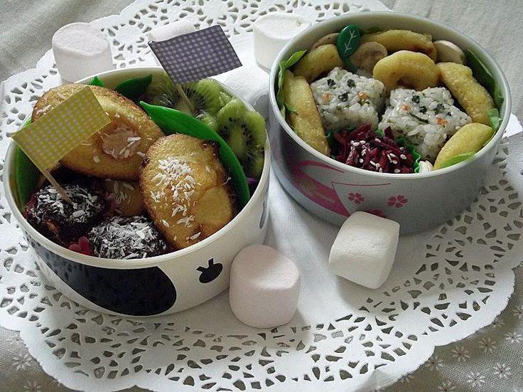 #14 Marie France Pour ce bento gourmand, j'ai préparé un repas équilibré avec des carottes violettes râpées, de petits onigiri au furikake et de la salade, des rondelles de champignons et des anneaux de calamars à la romaine.Et pour le dessert, on trouve un petit assortiment de douceurs : chamallows au chocolat et noix de coco, madeleines aux chamallows et caramel au beurre salé et de petites fleurs de kiwi !