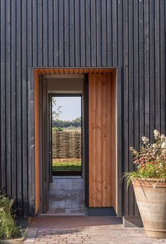 The Old Water Tower by Gresford Architects is two storeys high, with a gabled roof and a facade of black-stained timber weatherboarding.
