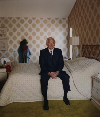Larry Sultan. Notice the mundane setting but the photograph is beautifully lit with strong natural light. Why not take photographs of someone at home in their environment. Ask them to sit / pose but no smiling at the camera.