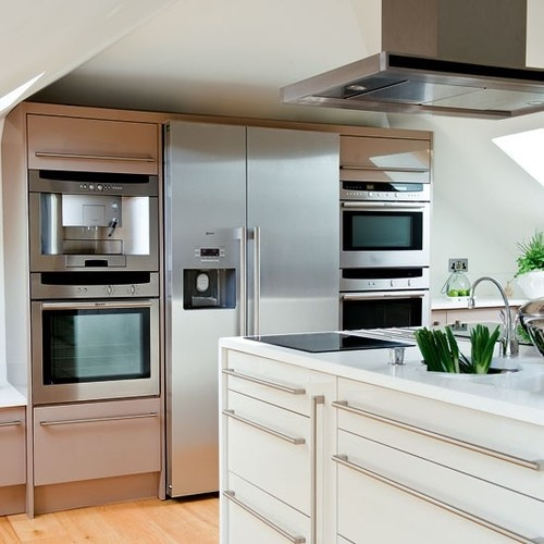 Kitchen Appliances The large fridge freezer is flanked by two built-in ovens, a combination microwave and coffee machine. An island extractor in stainless steel hangs over an induction hob on on side of the island and a domino hob on the other.