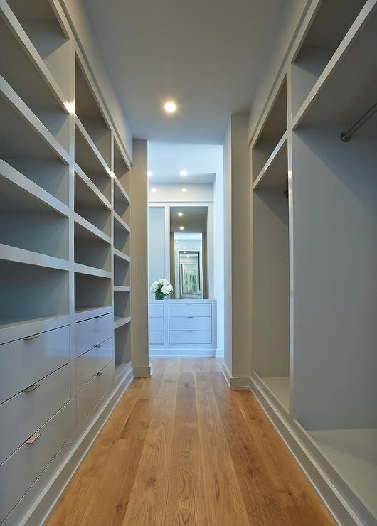 Gray walk in closet features gray open shelves, gray flat front drawers as well as gray clothes nooks.