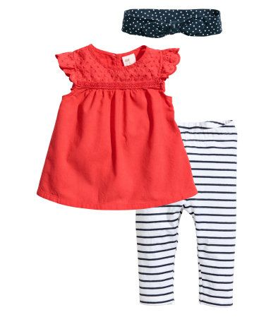 Coral red. Set in soft cotton with a dress, leggings, and hairband. Dress in airy, woven fabric with eyelet embroidery at top, opening with button at back