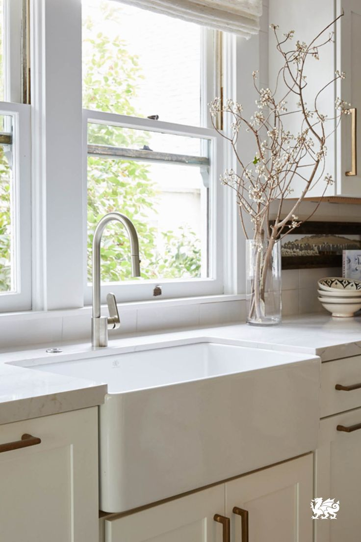 517 best kitchens images on pinterest a beautiful white farmhouse sink takes center stage in this monochromatic kitchen large windows
