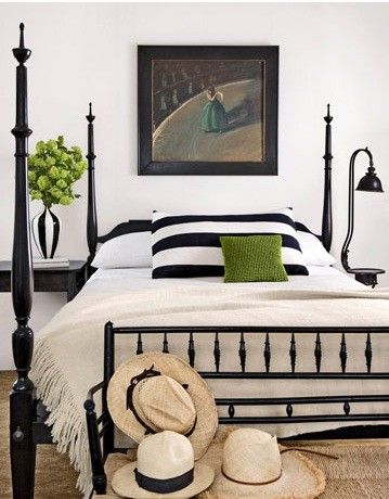 Black and white bedroom with black bed frame, striped pillow and vase, with pops of green color.  Fab!