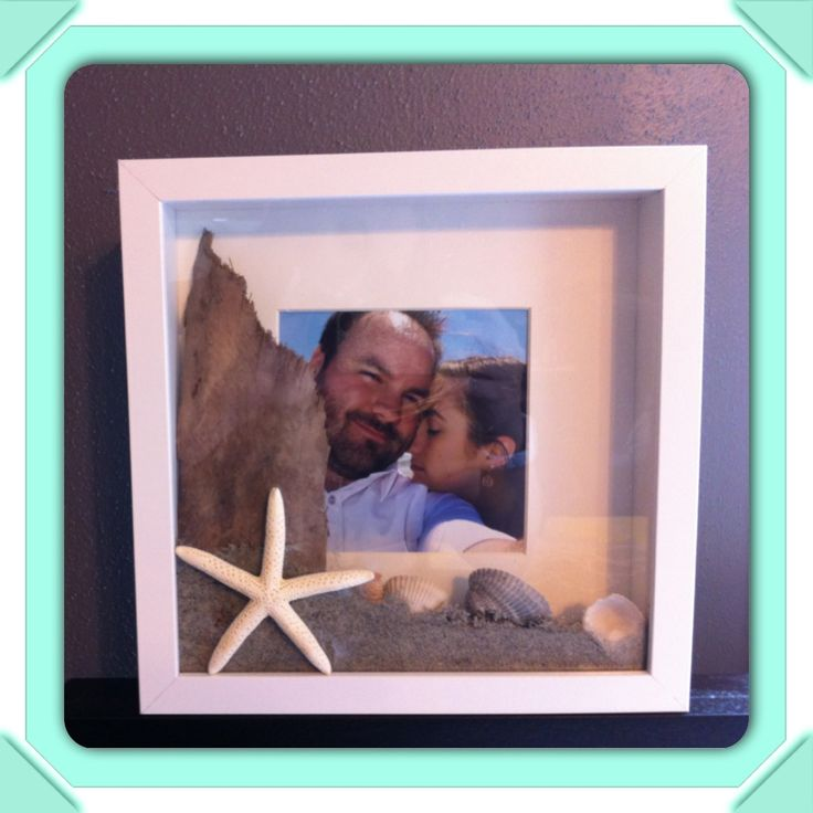 Sand and shells from the beach in a shadow box.