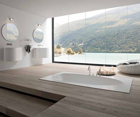 Modern minimalist bathroom with sunk-in bath, wooden floors and an outstanding view