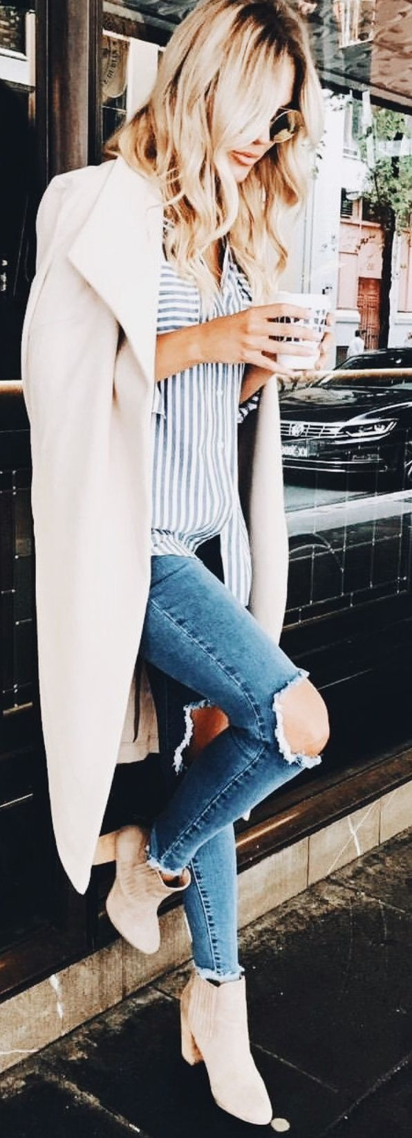 Tan Trench Coat, White/Blue Striped Button Down Top, Light Wash Ripped Jeans, Tan Ankle Booties.