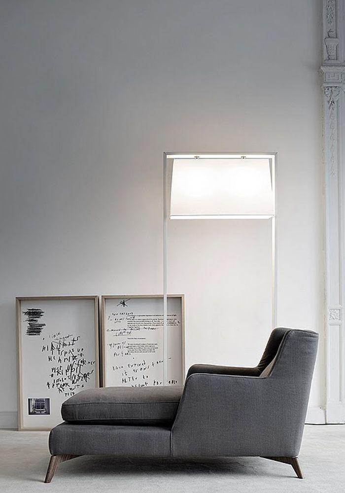 gianluigi landoni grey chaise lounge lighting wooded framed prints standing on light flooring grey walls