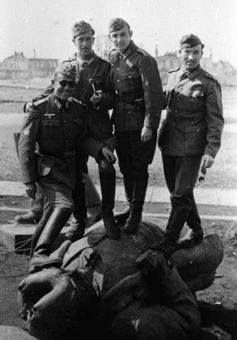 División Azul (Spain's Blue Division) soldiers stand a top of a broken communist monument in Russia, 1941-1942