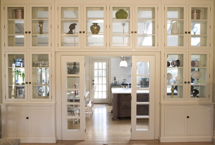 Glass display cabinets with bi-fold passage doors perfectly break up a large space all while providing storage solutions