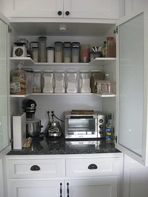 kitchen storage hidden behind a cabinet -- would be more functional if the doors slid back in so you didn't knock into them all the time.