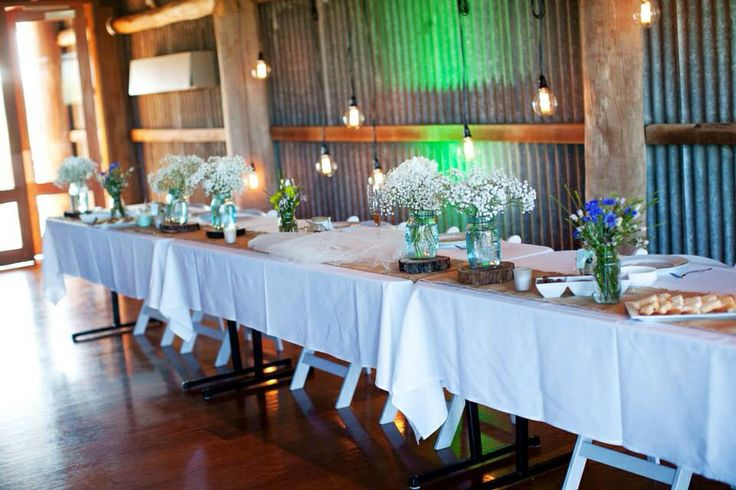 Rustic bridal table decor with pendant lights on feature wall. All made by us.