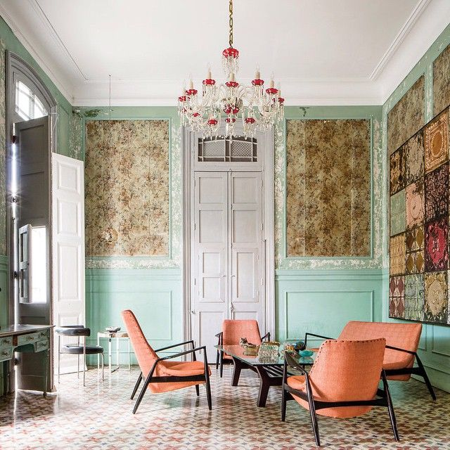 In the living room of the Havana villa owned by the Cuban artist Damian Aquiles and his American wife, Pamela Ruiz, midcentury furniture contrasts with wallpaper that predates the revolution. Swoon. Photo by Stefan Ruiz.