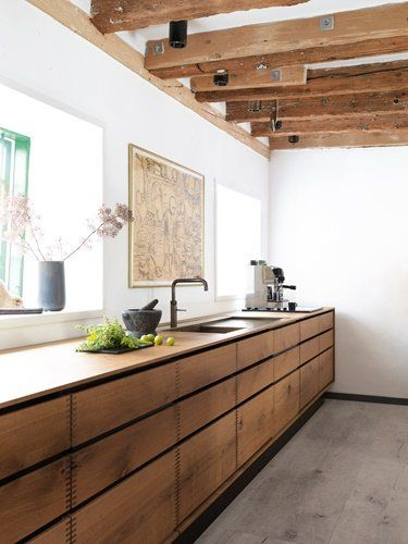 The kitchen's warmer color because it is treated with linseed oil. Note that the kitchen is made of continuous planks so that all trays in a layer comes from the same plank.Traditional Swedish handmade wood kitchen