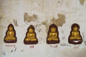 Four carved golden statues of Buddha in wall - Sami Sarkis/Photographer's Choice RF/Getty Images