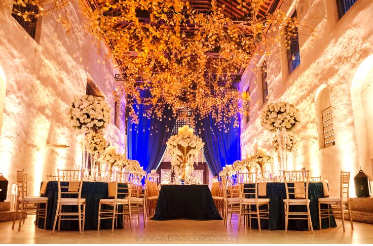Blue and gold are the colors of inspiration that Andres Cortes took for this wonderful wedding held in Sofitel Santa Clara in Cartagena. The shine of thousand of artificial gold leafs hold up in branches from the ceiling and blue is remarkable on the tablecloth, playing with raw flowers giving up the perfect color match. Design and decoration by Andrés Cortés.  #andrescortes #WeddingIdeas #Weddings