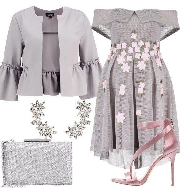 Outfit composto da vestito grigio con scollo a barca e applicazioni di fiori rosa, giacca corta con maniche ampie, sandalo rosa con listini, clutch argento e orecchini brillanti.