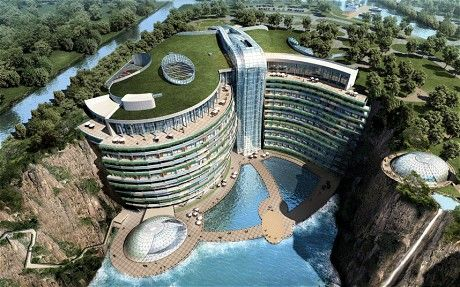 """""""In an abandoned quarry at the base of China's Tianmenshan Mountain, 30 miles outside Shanghai, an extraordinary hotel is taking shape. At a cost of £345 million, the InterContinental Hotels Group is building a five-star resort that will boast two floors above the top of the 330ft rock face and another 17 storeys below ground level, two of which will be underwater."""""""