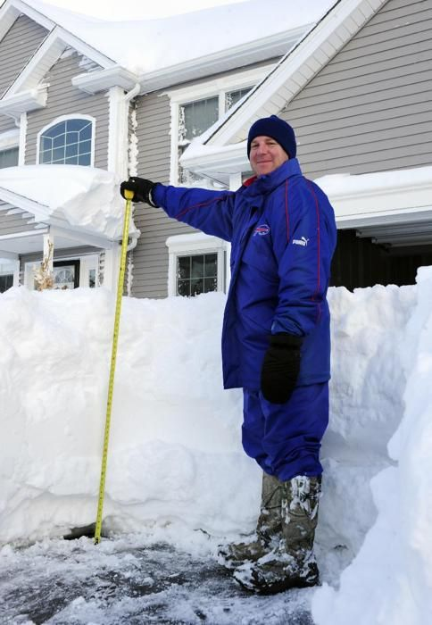 New York Art Hauret pauses after he measures the nearly four foot accumulation of snow in his driveway on Summerfield Drive in Lancaster, N.Y. Wednesday, Nov. 19, 2014. A ferocious storm dumped massive piles of snow on parts of upstate New York, trapping residents in their homes and stranding motorists on roadways, as temperatures in all 50 states fell to freezing or below