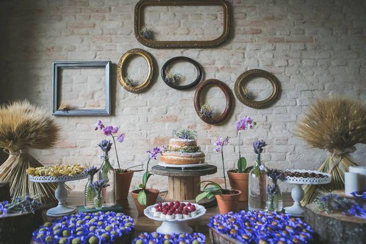 Casamento de dia com toques vintage com lavanda e trigo. Decoração romântica rústica com juta, tocos de madeira, caixotes de feira e objetos antigos como mala, relógios, molduras. mesa de doces orquídeas roxas