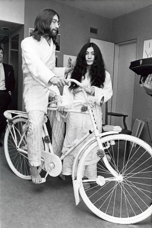 John Lennon with Yoko Ono-Lennon (riding a bike inside the Hilton Hotel in Amsterdam during his honeymoon, 27 March 1969. Photo by Ruud Hoff)