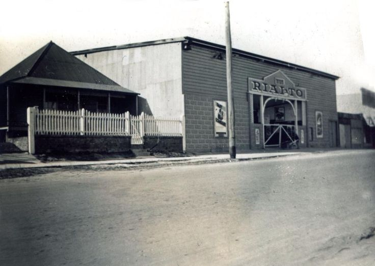 Title: Rialto Theatre, Downs Street, North Ipswich, 1942 Photographer: Unknown Geographic Location: North Ipswich, Queensland Date of Photograph: 1942 Description: The Rialto was in Downs Street near Fitzgibbon Street. T H Thomas opened the Rialto Theatre on 22 November 1919, he was also the owner of the Lyric Theatre at 150 Brisbane Street. Films would be advertised for both theatres and shared for different sessions. In July 1921 it changed management. On 17 December 1956 it was burnt…