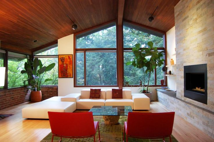 Potted trees make the most of the tall ceiling in the living room, adding dimension and new life to the space. A boxy sectional faces off with a pair of red chairs in the main seating area.