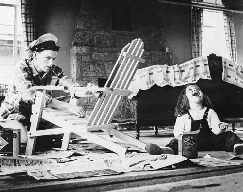 Frank Sinatra paints a chair in the living room of his Hasbrouck Heights, New Jersey home while three year-old daughter Nancy tries to catch food in her mouth, photographed by Peter Martin, 1943