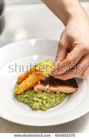 Chef is garnishing dinner plate with lemon