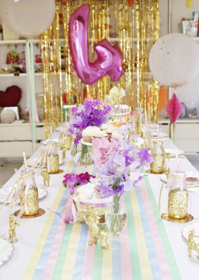 """Party table with long striped runner, floral elements, and glitter glasses from a Magical """"Magic is Four Real"""" Unicorn Birthday Party at Kara's Party Ideas."""