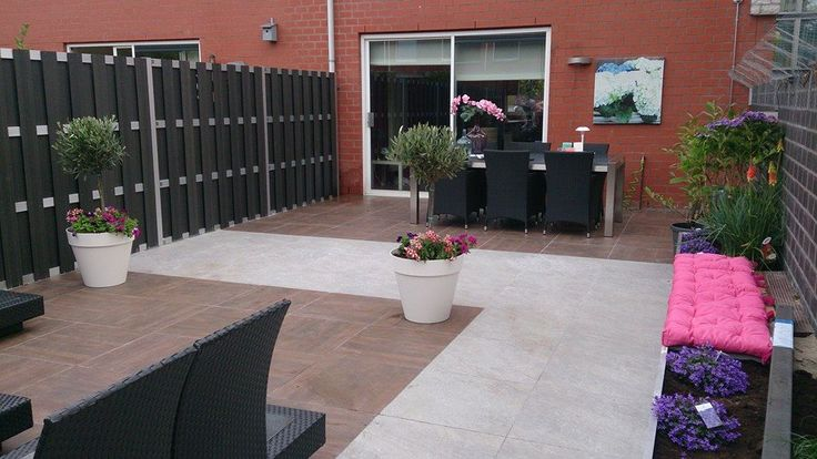 Een kleine achtertuin getransformeerd tot moderne onderhoudsarme lounge tuin.  De combinatie van keramische tegel in houtlook met een licht grijze tegel zorgt voor een speels effect en maakt de tuin optisch groter. Het gebruik van 2 contrasterende kleuren zorgt ook voor een scheiding tussen het zit / lounge gedeelte en het eet gedeelte.