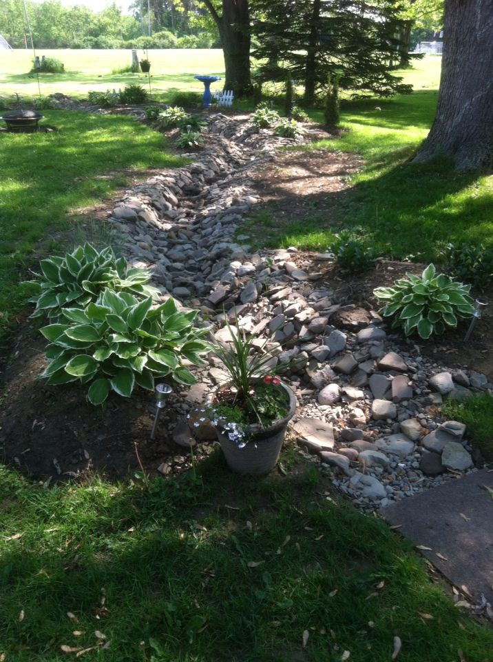 Dry creek with drain tile has improved water issues on back patio