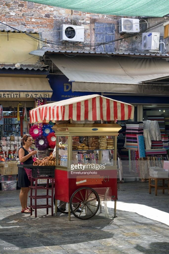 A street vendor with standardized red colored cart sells traditional pastry called 'gevrek' in the old shopping area of Kemeralti in Izmir.