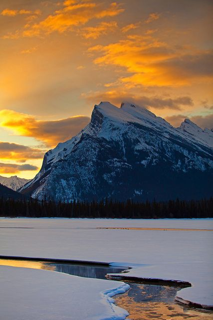 Sharp edges of the majestic mountains cut a silhouette against the colourful sky : Canada