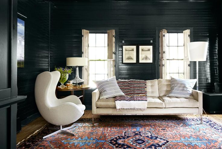 Dans le salon de cette maison Austin, les volets en bois clair pop contre le noir morose qui couvre les murs et les garnitures.
