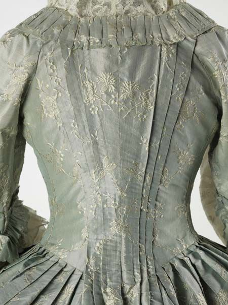 This gown and matching stomacher are made of very fine silk. Because of its shine or lustre, the fabric was called a lustring or lutestring. The process of 'lustrating' involved stretching and moistening the textile. In a 1756 treatise, silk designers are advised that ornaments for lustring 'must be open and airy' so as not to obscure the glazed ground. - Museum of London - ID no:57.106/8
