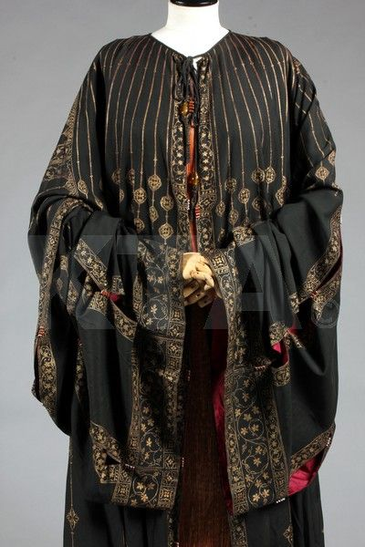 A fine and rare Mariano Fortuny stencilled orientalist black silk evening coat, circa 1910-20, with circular label applied to the wine silk lining, stencilled in gold with delicate foliate traceries with vines and grapes, the wide panelled sleeves and skirts linked by striped glass Murano beads, tie cords to neck