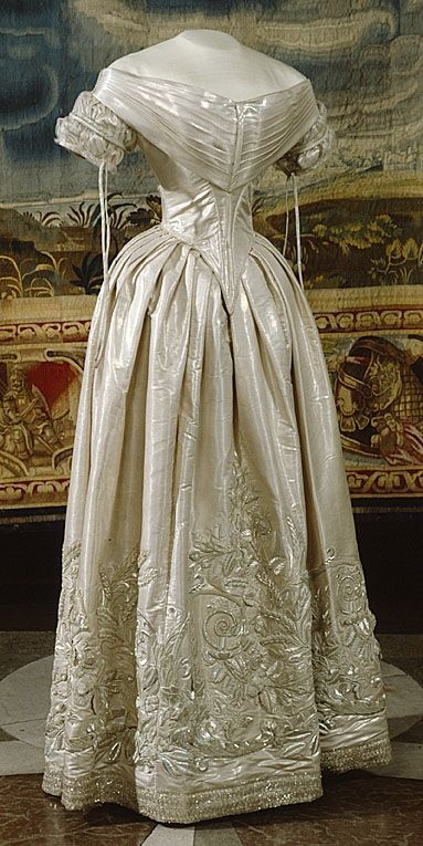"Wedding dress (bodice, skirt, train) of Queen Queen Lovisa of Sweden, née Princess Louise of the Netherlands, 1850. Silver woven silk with silver embroidery. Pleated bertha collar in front, tulle-covered ""lattice"" sleeves."