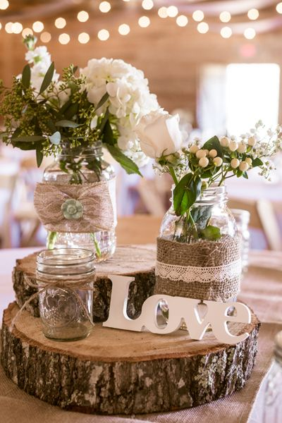 Stack burlap-wrapped Mason jars atop tree trunk slices.Easy  & Inexpensive mason jar projects for your wedding!  Buy inexpensive wedding flowers delivered from www.bulkwholesaleflowers.com #masonjars  #weddingflowers #wholesaleflowers