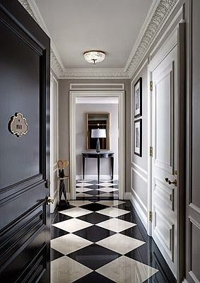 i like the woodwork floors and the grayish paint color of wall with the black door and black and white floor