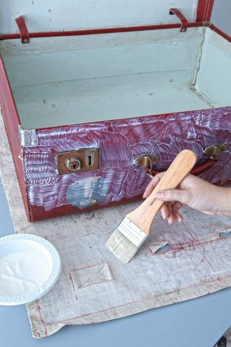 instructions and photos on how to decoupage fabric onto a suitcase