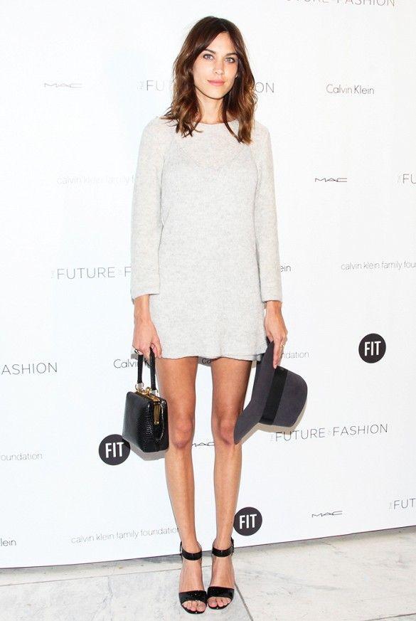 Alexa Chung wears a beige sweater dress, black heeled sandals, a fedora, and mini box bag