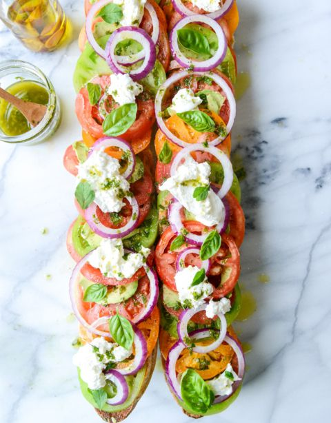 heirloom tomato, avocado and burrata grilled garlic toast 1 large baguette, sliced in half 6 tablespoons roasted garlic oil 3 to 4 heirloom tomatoes, thinly sliced 2 avocado, thinly sliced 1/2 red onion, thinly sliced 2 balls fresh burrata cheese fresh basil and oregano leaves for topping