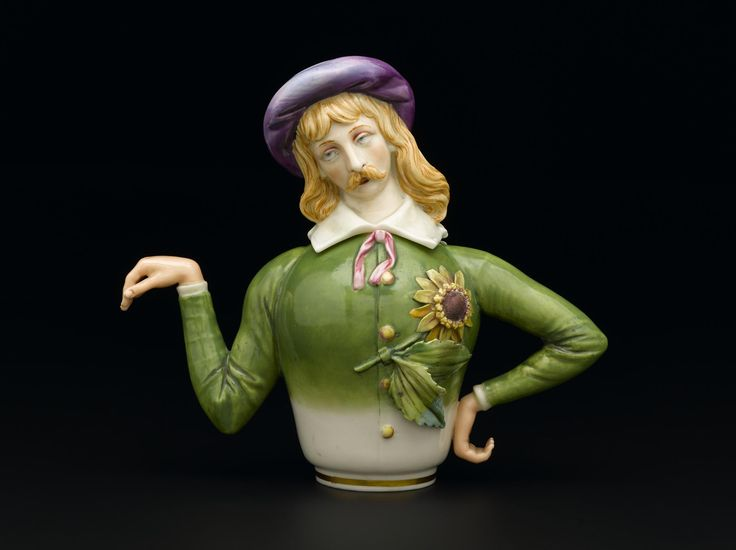 Aesthetic teapot with lid, painted porcelain in double sided form, with on one side a flamboyant young man wearing a sunflower and on the other a woman wearing a lily, both in Aesthetic dress, modelled by James Hadley and manufactured by Royal Worcerster, British, 1882