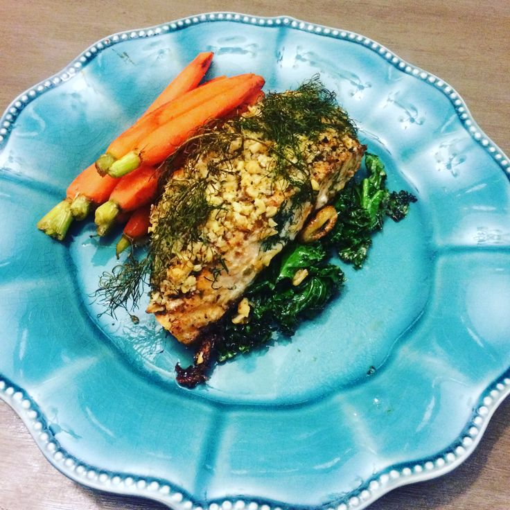 Walnut crusted salmon in a bed of sautéed kale with steamed carrots