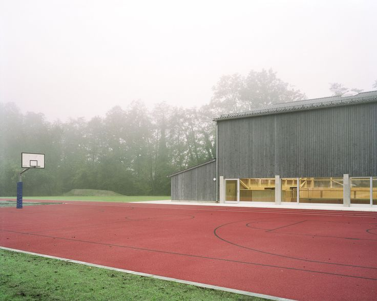 Wooden trusses pattern walls of prefabricated sports hall by Florian Fischer